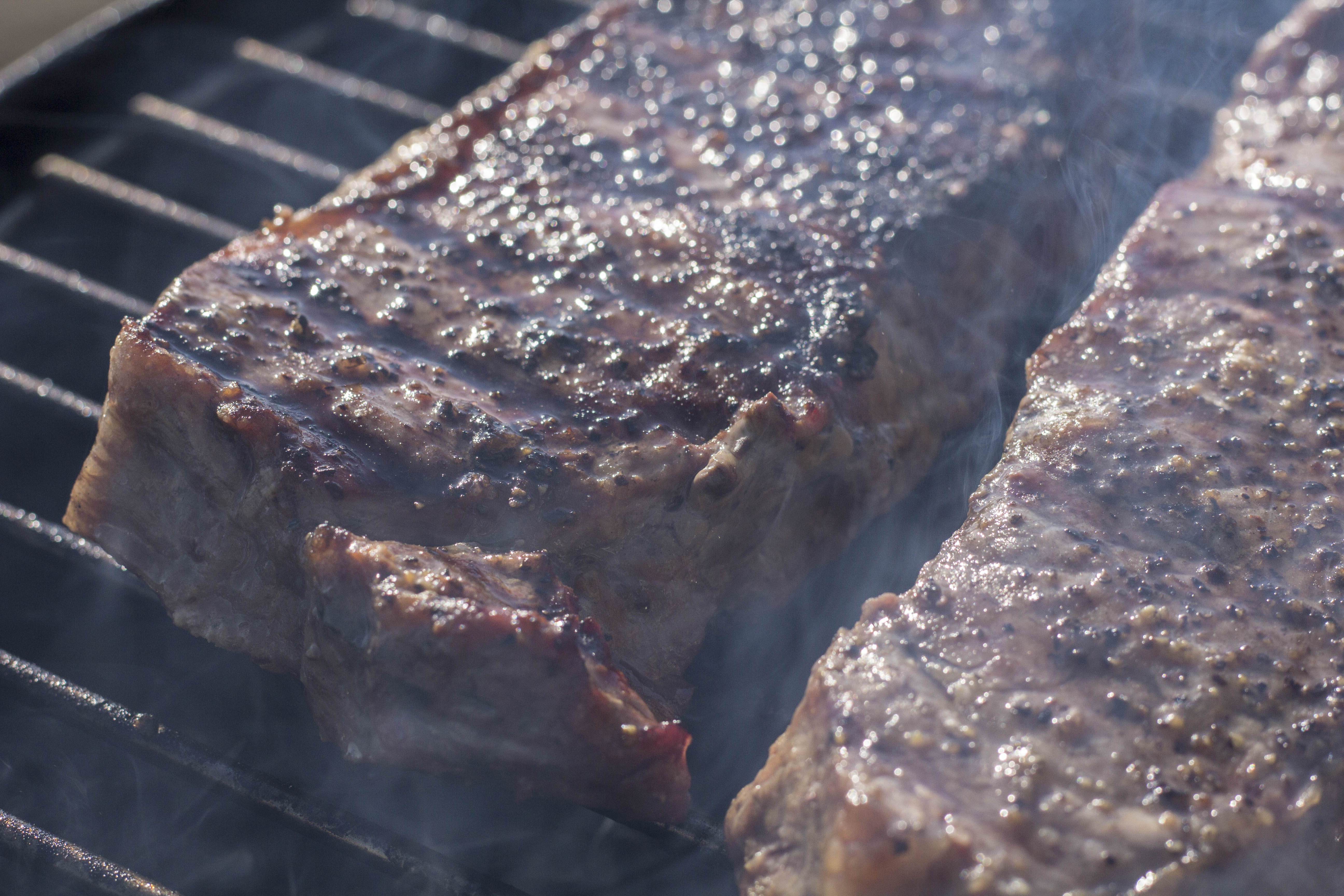 steaks smoking on a grill